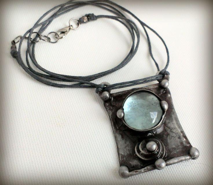 Cínovaný šperk ozdobený skleněným namodralým kabošonem. Z autorské dílny Qtáček.