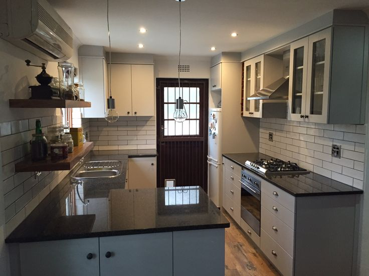 Kitchen Renovation completed in Stellenbosch.  - Grey melamine built in cupboards - Rustenburg black kitchen tops - Solid kiaat floating shelves - Smeg gas hob, chimney extractor and oven. - Settecento rustic blanco mat glazed ceramic wall tiles - Fossil wood glazed porcelain tiles