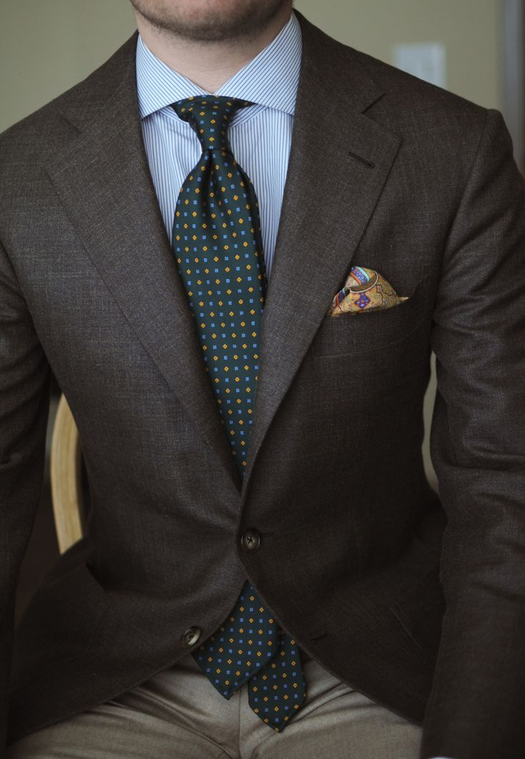 Brown sport coat, white shirt with light blue pinstripes, green tie, khakis