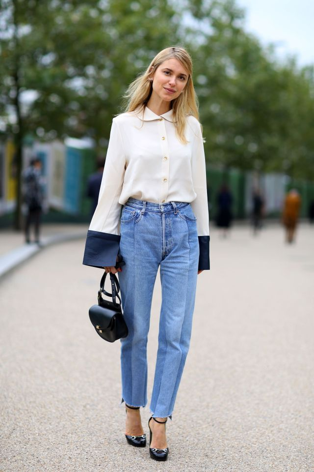 A street style star in a J.W. Anderson blouse, Vetements jeans, and black Gucci heels and denim at London Fashion Week 2015.