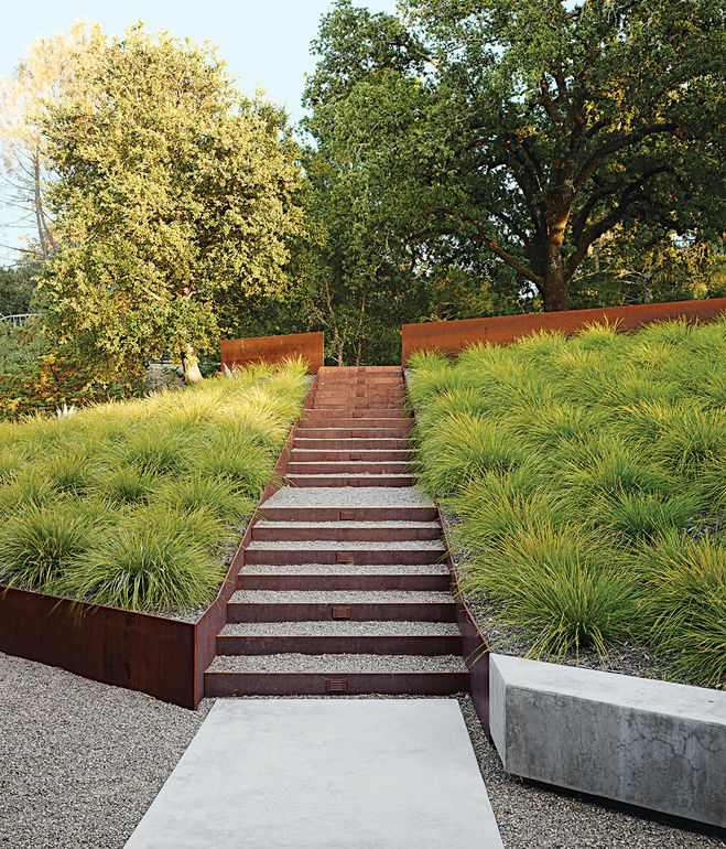 Plant choice. Lomandra— an Australian herb—flanks a Cor-Ten steel staircase and a walkway lined with Yosemite tan pebbles and concrete.