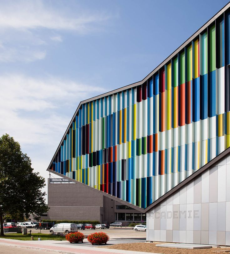 Academie MWD Dilbeek by Carlos Arroyo,Dilbeek, Belgium. System of louvres to the facade so that, like a lenticular image, the appearance differs depending on the viewing angle. The rear of the building is clad in a similar variation of metal panels with contrasting finishes.