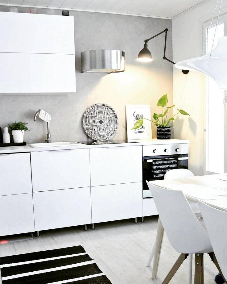 Kivoja pieniä musia ja metallisia yksityiskohtia keittiön valkoisessa sisustuksessa