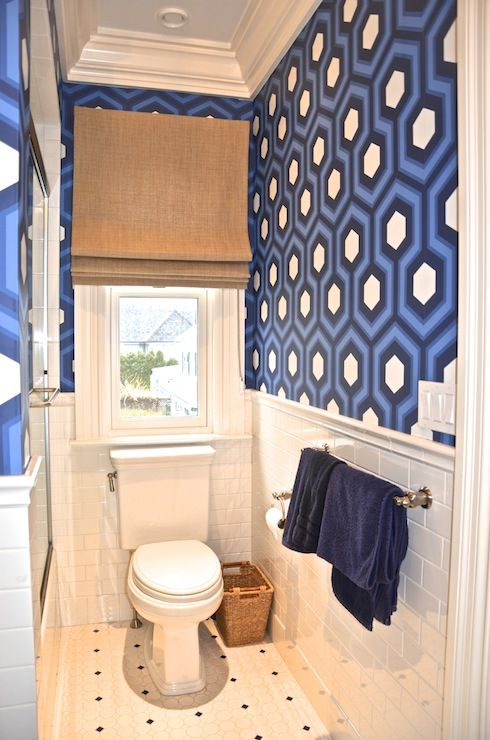 Blue boy's bathroom with tray ceiling painted sky blue and blue hex wallpaper by David Hicks paired with white subway tiled walls over vintage tiled floor, Bathroom features toilet under window covered in natural woven roman shade.