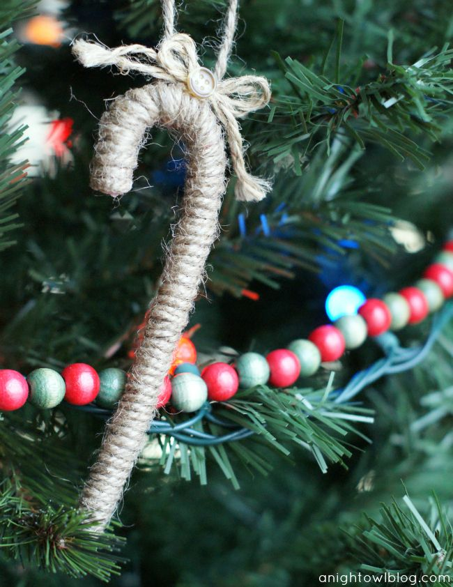 DIY Twine Candy Cane Ornament at @anightowlblog - Just use spray adhesive and wrap a candy cane with twine. Add a loop at the top for hanging and a bow with a button to finish it off! #trimyourtree