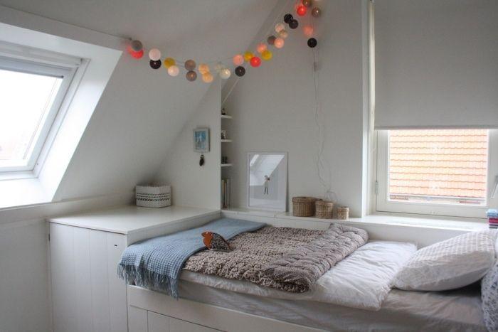 chambre sous combles avec un lit et peinture murale blanche