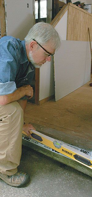 """In this """"Building Skills"""" article, senior editor Andy Engel describes how to install a prehung exterior door. To start, he checks the wall and sill for level, and installs shims as needed. Then, after placing beads of sealant across the length of the rough sill, he sets the door in the opening. Driving one screw through the door trim near the top hinge keeps the unit from toppling while it's being shimmed plumb. Next, after shimming them, Engel fastens the hinges to the framing. The next…"""