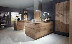 Moderne, houten keuken met grijstinten. Deze moderne keuken krijgt een landelijke toets door gebruik te maken van hout in de keukenkasten en kookeilandjes. De keuken bestaat uit twee aparte eilanden die aan de muur zijn verankert, het ene eiland is voorzien van een werkblad met gootsteen, de andere heeft een kookplaat, werkblad en rechthoekige dampkap als design element. De donkere houtkleur en de donkergrijze muren zorgen voor een warm en gezellig gevoel in de keuken.