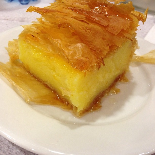 GALAKTOMPOYREKO Galaktobureko (Greek: γαλακτομπούρεκο) is a Greek dessert of semolina-based custard in phyllo. It may be made in a pan, with phyllo layered on top and underneath, or rolled into individual servings (often approximately 10 cm long). It is served or coated with a clear, sweet syrup. The custard may be flavored with lemon, orange or rose.