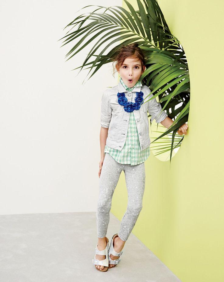 J.Crew girls' white denim jacket, everyday leggings in splatter print, fringe flower necklace, and Birkenstock Arizona sandals.