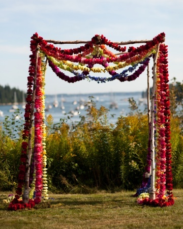 A Rainbow Of Garlands: Single-color flower garlands are strung together to create a rainbow effect on a birch wood ceremony structure. It is a nod to the initial inspiration: an Indian wedding where it's traditional to have strings of carnation garlands.
