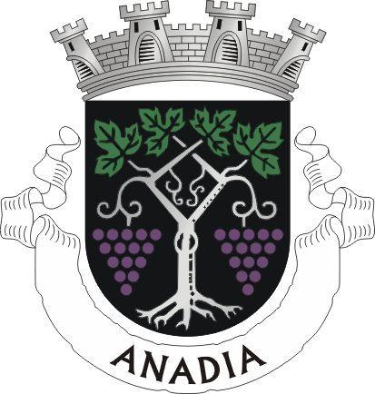 """Civic heraldry of Portugal - Brasões dos municípios Portugueses Official blazon  Escudo de negro, com uma vide de prata com dois ramos passados em aspa, folhados de verde, e frutado de dois cachos de uvas de púrpura, uma de cada lado. Coroa mural de prata de quatro torres. Listel branco com os dizeres : """" ANADIA """", de negro.   The arms were officially granted on June 1, 1959."""