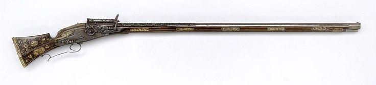Anonymous | Radslotgeweer, Anonymous, c. 1625 | Radslotgeweer of radslotmusket. Het ijzeren slot  heeft gedraaide en gegoten onderdelen; het klein rad is gevat in een ring die aan de plaat is vastgemaakt. De ijzeren loop is op de achterste helft in hoog reliëf geciseleerd met drie ovale cartouches met naakte menselijke figuren waaronder waarschijnlijk Adam en Eva, geïncrusteerd in zilver; voorzien van gekraalde versieringen in geometrische patronen en van bloemenranken; de vizierkorrel is…