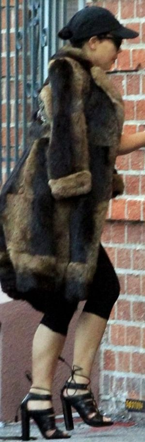 Who made  Kim Kardashian's black hat, brown coat, and lace up sandals?
