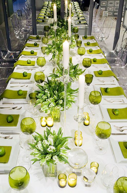 Lime green linens and glassware punctuate a crisp white tabletop lined with green and white blooms.