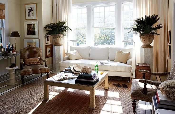 """William's favorite spot is the serene living room, which is flooded with light in the morning. """"My dog, Baylor, and I usually sit in there on the sofa, and I check emails and drink my coffee,"""" he says. A braided jute rug defines the seating area and separates it from the dining area. William often rolls up the rug and paints canvases on the striped floor."""