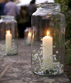 Frasco de vidrio, vela y flores.