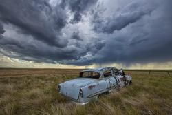 an old abandoned Chevy watching a thunderstorm in Saskatchewan