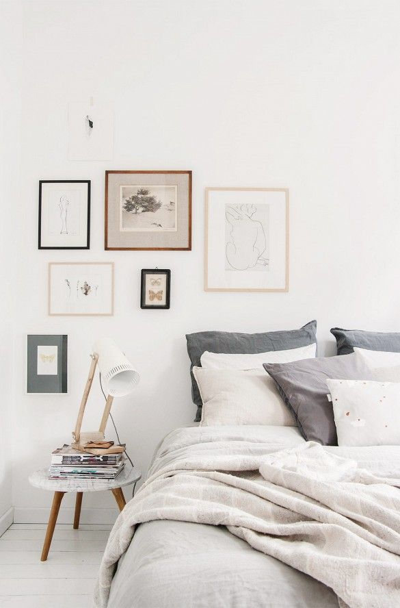 Small gallery wall above bed in neutral bedroom with white walls