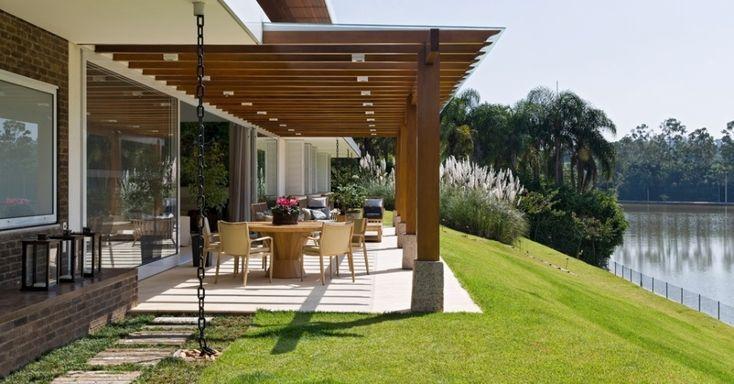 """A área que antecede a varanda, voltada para o lago, conta com um pergolado de madeira garapeira coberto por vidro laminado """"crystal clear"""" com 18 mm de espessura. Os pilares de madeira ficam apoiados sobre blocos maciços de granito, a fim de evitar o apodrecimento. A casa LM/RM, no interior de São Paulo, tem arquitetura do escritório CVA"""
