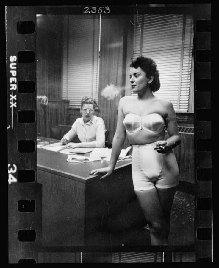 Lingerie model, wearing a girdle and strapless bra, smoking in an office; in the background a woman sits at a desk.(Stanley Kubrick, photographer, LOOK Magazine Photograph Collection, Library of Congress, Prints & Photographs Division,) - Photos: How Stanley Kubrick Saw Chicago In 1949: Chicagoist