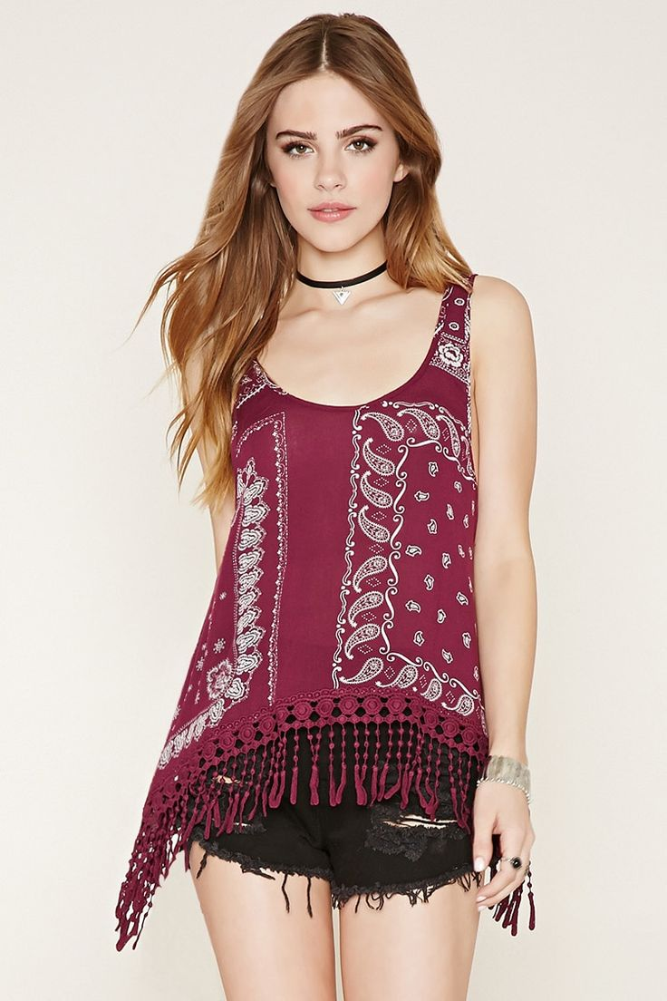This sleeveless woven top features a prominent trapeze silhouette, an allover paisley print, a crocheted tassel hem and a round neckline.