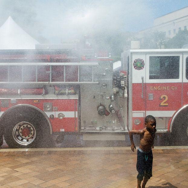 Un bambino si rinfresca con il getto d'acqua proveniente dal camion dei vigili del fuoco a Washington, negli Stati Uniti