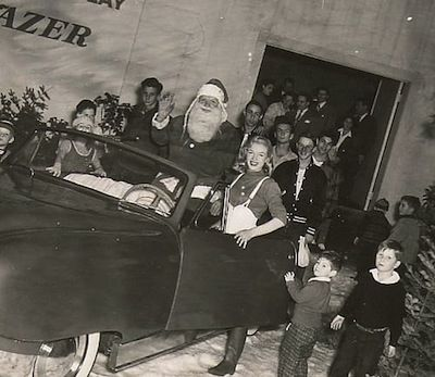 "Marilyn Monroe & ""Santa Claus"" participating in a publicity event to promote the new Darrin/Kaiser-Frazer car, 1946."