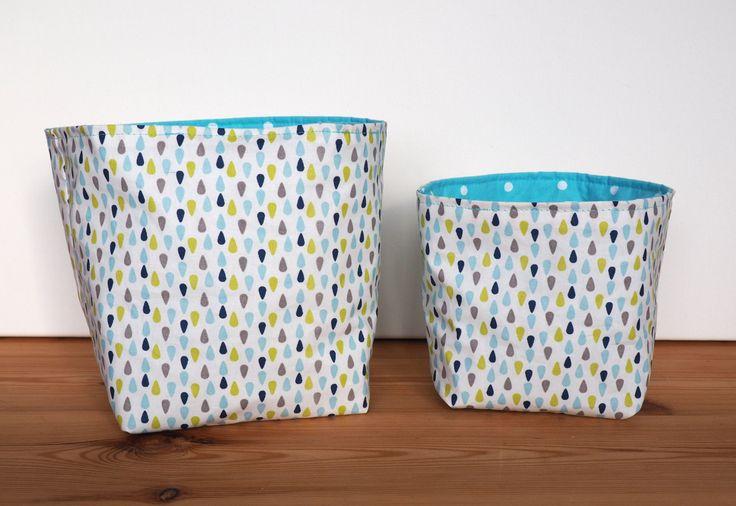es deux paniers sont en coton enduit imprimé de gouttes bleu clair, bleu marine, verte et grise sur un fond blanc. De lautre, ils sont en coton bleu clair à pois blanc.  Lavantage du coton enduit est quil est imperméable et se nettoie dun coup déponge. Ils sont triplés avec un entoilage pour plus de tenues. Ils peuvent vous servir comme rangement dans votre salle de bain, comme vide-poche, ou rangements divers et variés tout en décorant votre intérieur. Ils feront aussi leur petit effet dans…