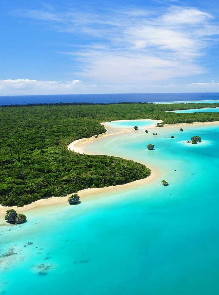 Lush green landscape and blue waters of New Caledonia ~ http://suitcasesandsunsets.com/new-caledonia.html