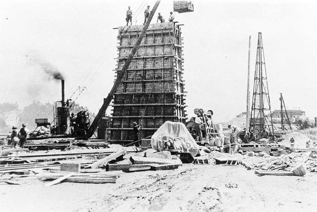Construction of piers for bridge at Murray Bridge, with men standing on top, and a large block being lowered by crane, Murray Bridge, South Australia, 1920