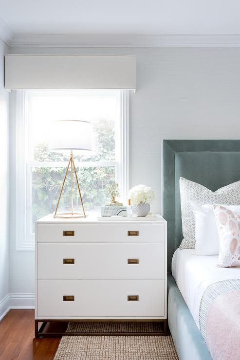 Pink-blue bedding, blue velvet headboard and jute area rug are paired with a white nightstand dresser and brass pulls.