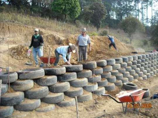 Retaining wall made out of old tires. God knows we need a good way to reuse them....