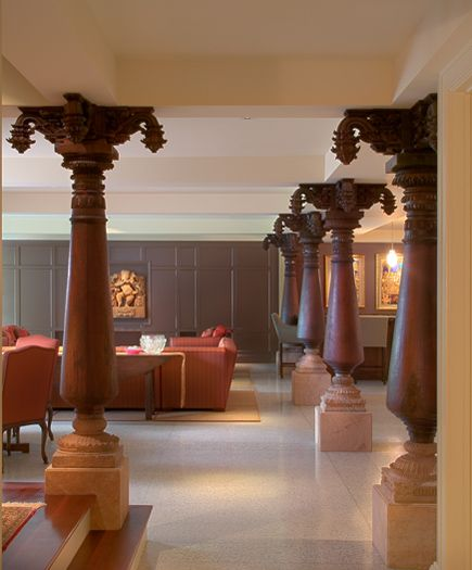 Eighteenth Century Columns from a courtyard house in Delhi have been repurposed to conceal the steel structure in this Lower Level Entertaining Room. Richly colored walls and terrazzo floor set off these carved wood features. Photo by George Dzharistos.