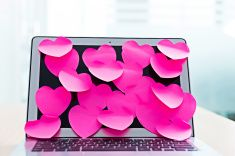Laptop screen covered by heart shape adhesive notes stock photo