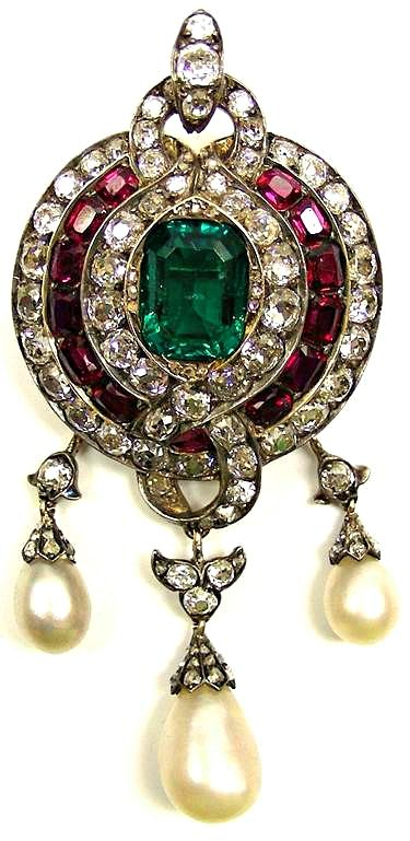 19th century emerald, ruby, diamond & pearl pendant brooch, English c.1860, centred by a trap cut emerald in a triple border of diamonds, rectangular rubies & diamonds, scroll diamond hoop to top and bottom, suspending three drop shaped pearls from foliate diamond links, open set in silver and gold.