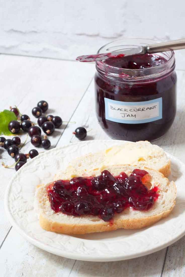 Jar of blackcurrant jam by recipesmadeeasy with a plate of bread and jam in the foreground.