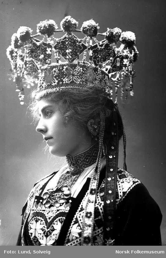 Digitalt Museum - Studiofotografi av kvinne kledd i brudedrakt og brudekrone fra Hordaland. Brystutsnitt. Vendt mot venstre. Ser ut mot venstre. Fotograf: Solveig Lund