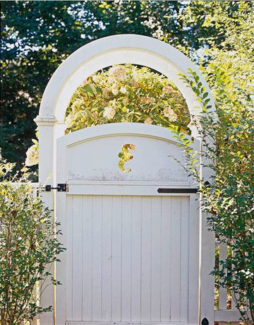 white garden gate and arch with seahorse cut-out. hydrangeas bloom in the back. classic Hamptons garden gate.