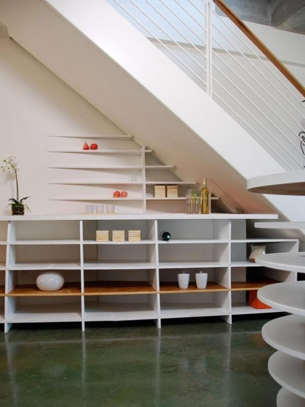 No time for built-ins? Stack shelves or a credenza under your stairs for a sleek look. | 27 Genius Ways To Use The Space Under Your Stairs
