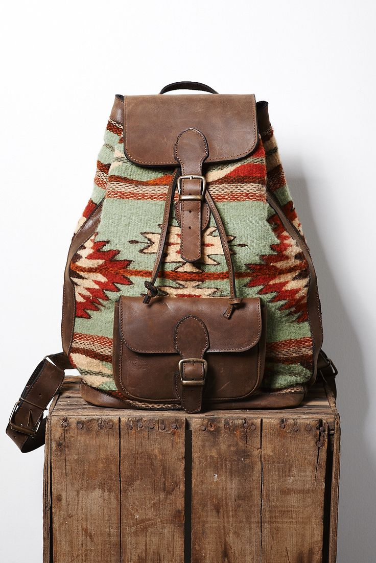 The 'Forest Glenn' backpack features Zapotec butterfly, agave, lightning and arrow designs in earthy orange and red on moss green. You can access your stuff via the cinch opening at the top or a conve