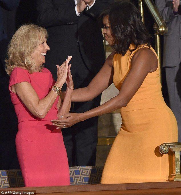 Obama (right) hugs Jill Biden, wife of Vice President Joe Biden, who is dressed in a brigh...