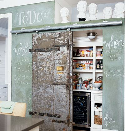 A salvaged sliding door conceals this pantry, where generous storage keeps kitchen necessities readily accessible.