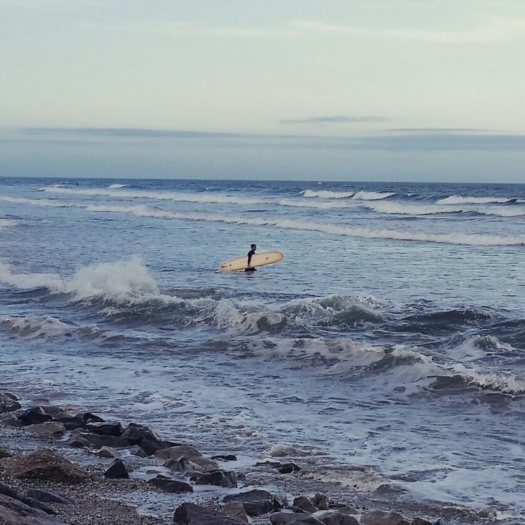 Into the blue. Surfer taking advantage of higher waves in Surfside Texas.
