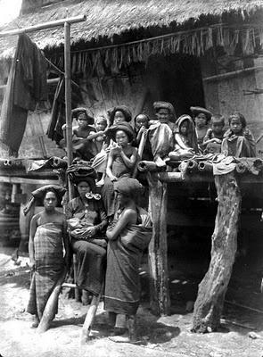 Een Karo-Batak familie op de toeré de galerij die rond het huis loopt Noord-Sumatra | 1911-1919
