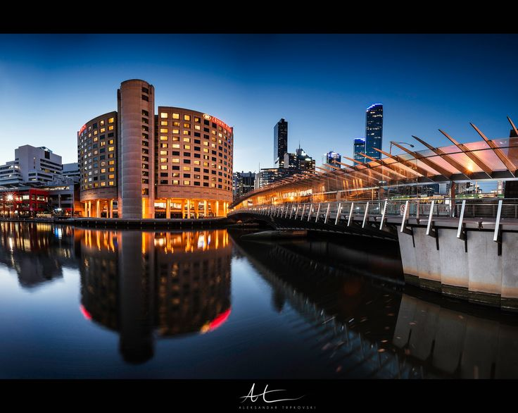 Visit www.AleksTrpkovski.com for more details - It was a cloudless autumn night last Saturday here in Melbourne. I went to the city scouting for a nice cityscape composition to photograph. I found this location near the Melbourne Exhibition Centre worked best for the photo I imagined. I love how the bridge is leading your eyes towards the Crowne Plaza Melbourne building and how its lights reflect into the water. The blue and orange complementary colours paired perfectly together and give you…