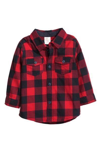 Een hemd van geweven katoen met een kraag, een knoopsluiting, borstzakken met klep en knoop, en lange mouwen met manchet en knopen. Het model is onderaan li