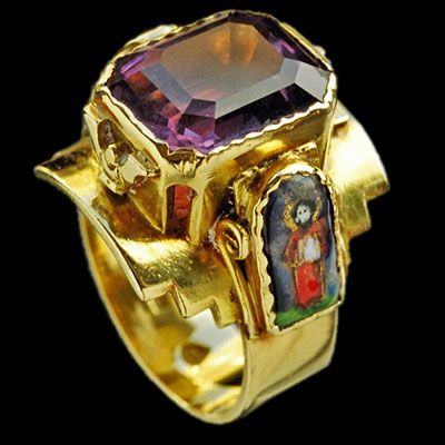ECCLESIASTICAL Superb Arts & Crafts Ring   Gold, enamel & amethyst  Length: 2.2 cm  Width: 2.5 cm  (Length: 0.8 in)   Monogram: 'GB' with a cross within a shield  British. Circa 1910  One enamel panel restored  Fitted case  Literature: cf. Artists' Jewellery, Pre-Raphaelite to Arts & Crafts