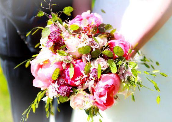 Bruidsboeket in de stijl van een veldboeket met pioenen, sierhaver, judaspenning, astrantia, lichtroze rozen en astilbe