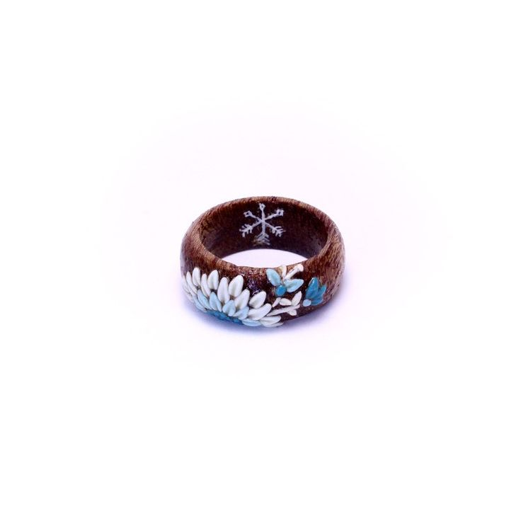 A blue polymer clay flower on a wooden ring symbolizing calmness by Huntress & Hunter